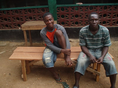 Paul and Ruben sit on new benches they made