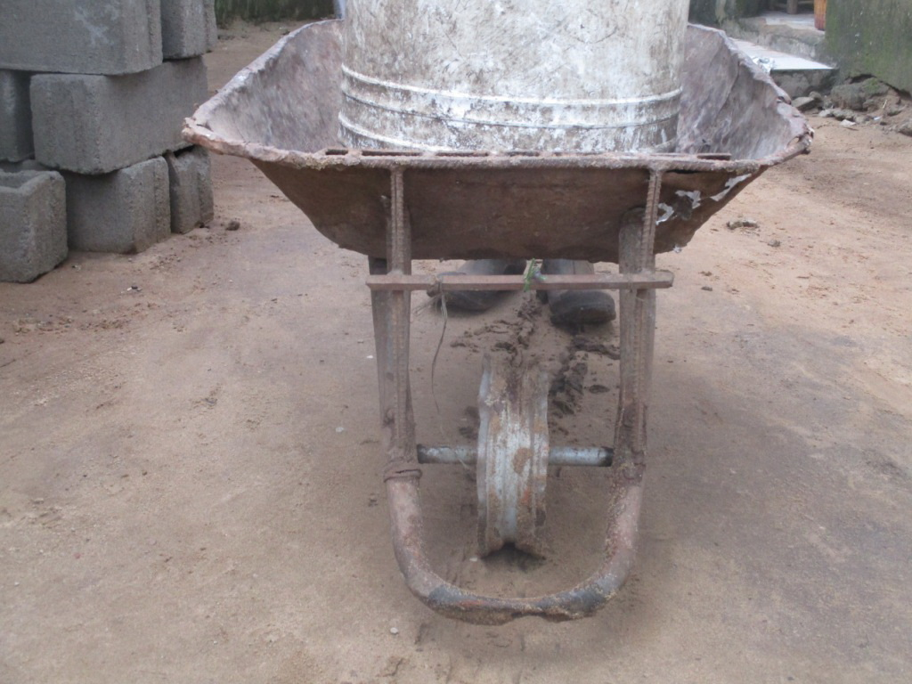 Photo of Otis' wheel barrow with only a rim making his job very hard.  His boots have holes so when he walks through sewer or bad water his feet get wet.