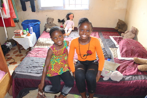 Promise and Bernice sitting on their bed. Their rooms were all tidy and clean!