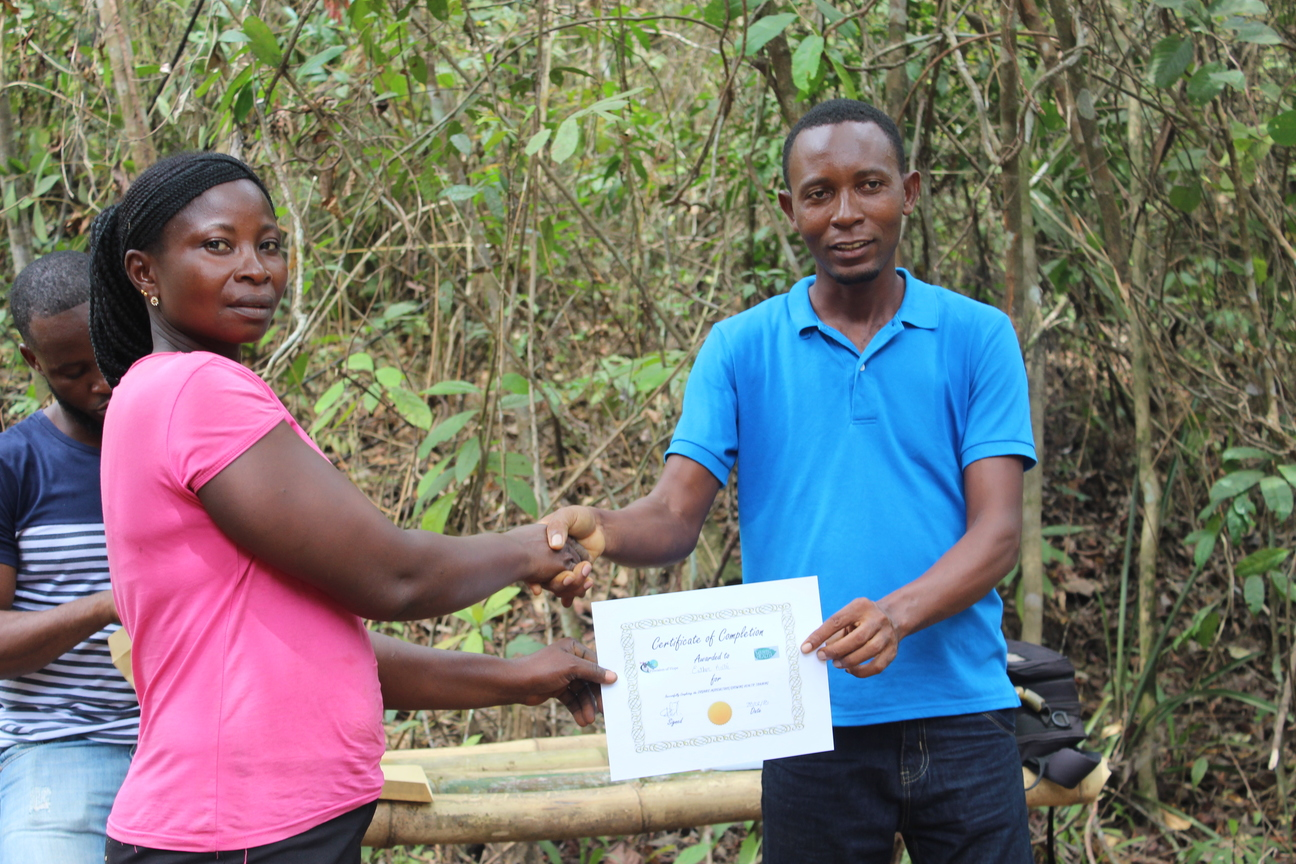 Kelvin Taweh hands a certificate to each farmer.