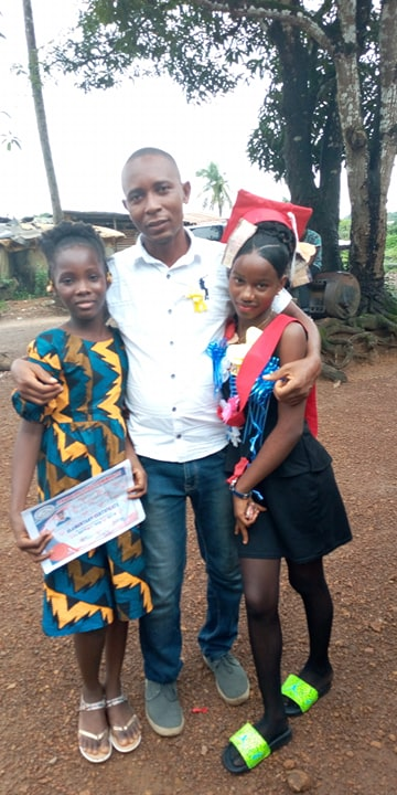 LOVETTE Gr. 6 and VIOLA Gr. 7 standing with our Kelvin Taweh.  Both girls are being raised by single mothers.