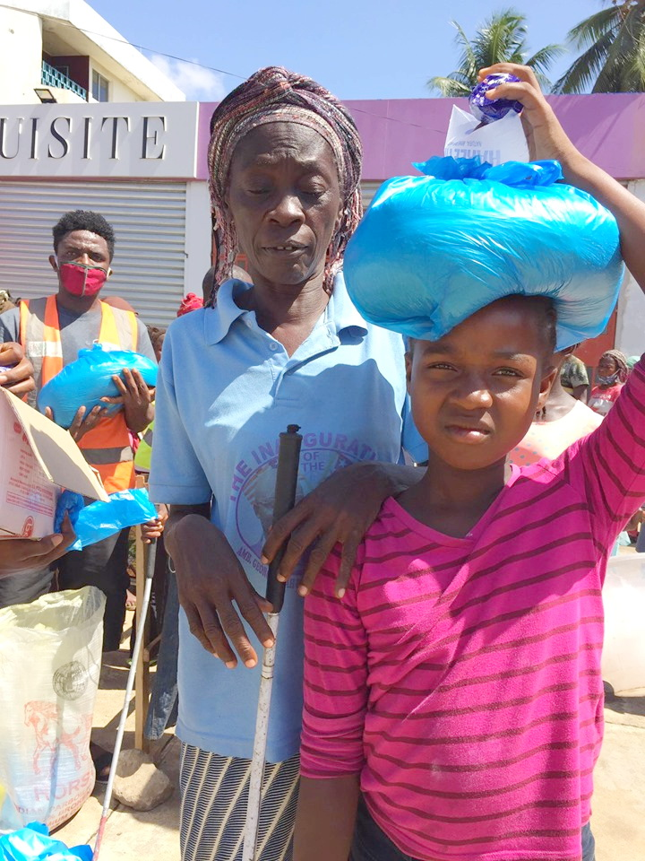A young girl leads her blind mother to get her food portion.