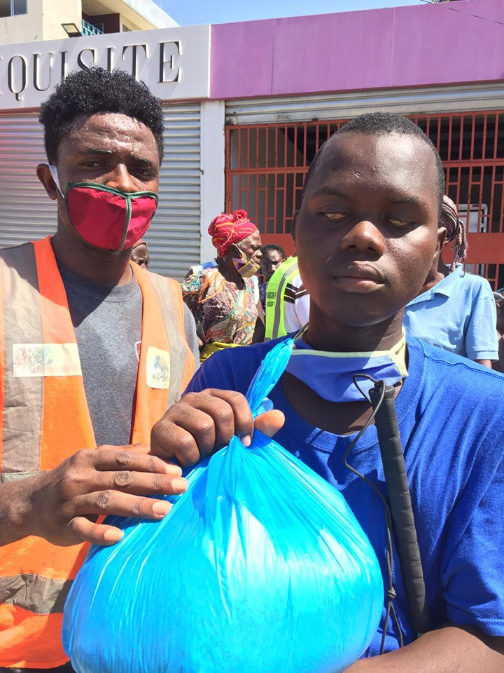 Jeremiah, one of our volunteers, giving a food package to a blind man.