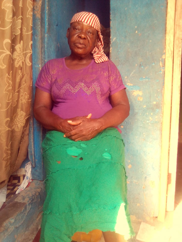 Mama Mabel Constance sitting in front of her little place.