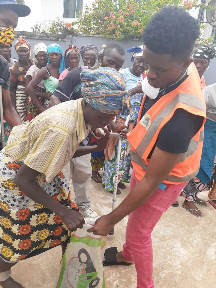 Jeremiah Gaye, one of our volunteers, is distributing rice to a disabled woman.