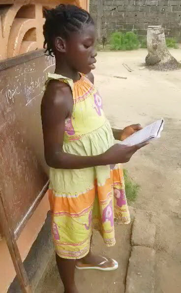Favor is reading her assignment to the class.