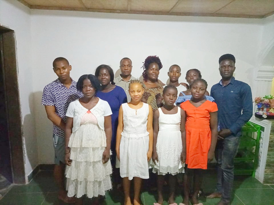 This is a family photo of Benjamin and Angie with their children. 2 of the children were not in this photo. The children's ages range from 10 yrs to 20 yrs. They are funding them all to school on their own.