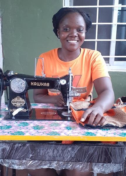 Maima David is loving her new machine.  Here she is sewing a dress! Keep up the good work Maima!